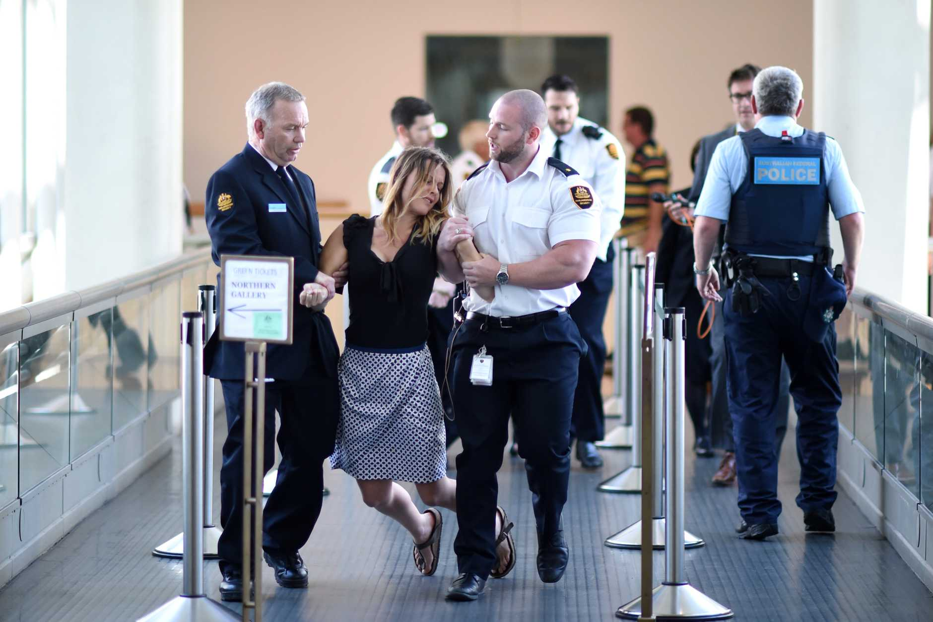 Security guards carry a protester out of the House of Representatives at Parliament House in Canberra, Wednesday, Nov. 30, 2016. Question Time was adjourned due to pro refugee protesters interupting proceedings.