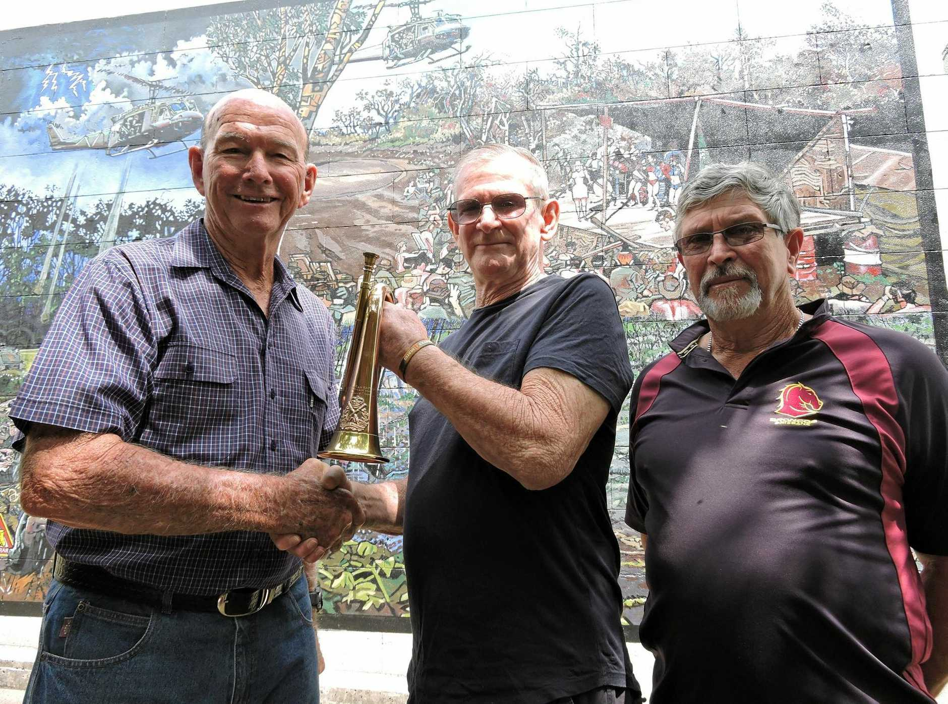 HANDOVER: Maryborough Military and Colonial Museum volunteer John McCoombe accepts the  bugle from  Rob and Mark Kidner.