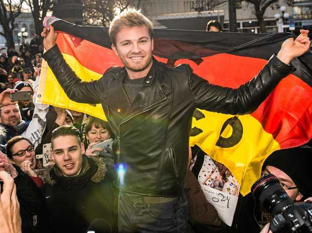 World champion Nico Rosberg with a German flag surrounded by fans in Wiesbaden, Germany.