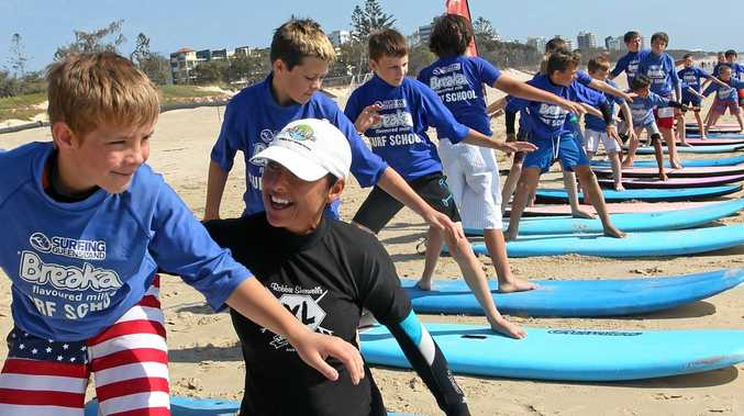 Carlene Sherwell in black, instructing young learner surfers at Alexandra Headland.