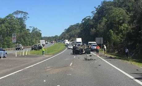 A car on its roof after a three-vehicle crash on the Bruce Highway.