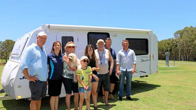 Cr Jason OPray, park manager Tanya McSorley, Wendy Cooper with Daisy the dog, Isabella and Sarah Cooper, George Cooper, park manager Darren McSorley, council Manager Commercial Geoff Close with the Coopers' caravan