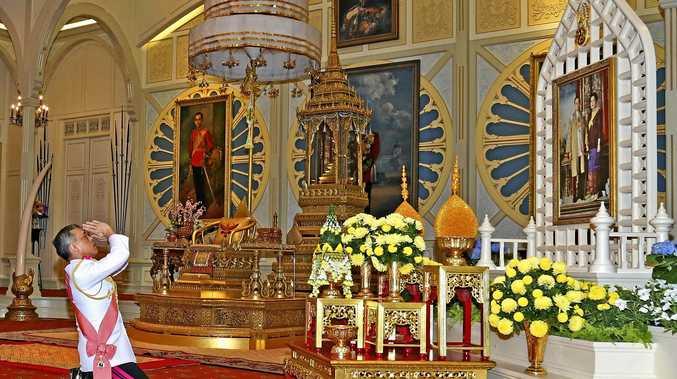 King Maha Vajiralongkorn Bodindradebayavarangkun pays his respects before a portrait of the late Thai King Bhumibol Adulyadej and Queen Sirikit at the Dusit Palace in Bangkok.