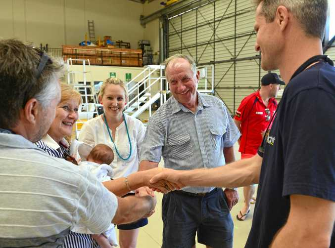 Allan McKeering shakes aircrew officer Rick Harvey's hand while his wife Carmel shakes the pilot's hand when they reunite after a serious accident to Allan. Allan's daughter who witnessed the accident, Annaleise Koolstra looks on and her son Fletcher is with Carmel.