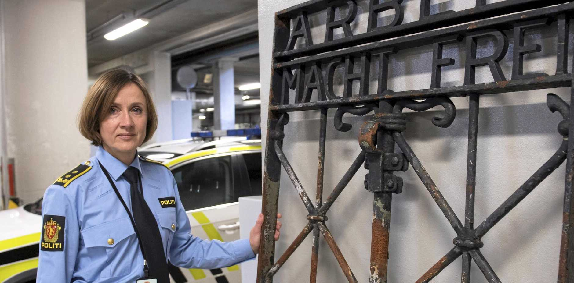 Kari Bjoerkhaug Trones stands next to the iron gate from the former Nazi concentration camp memorial site in Dachau.