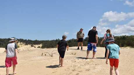 Tourists walk around Lightning Ridge on Moreton Island