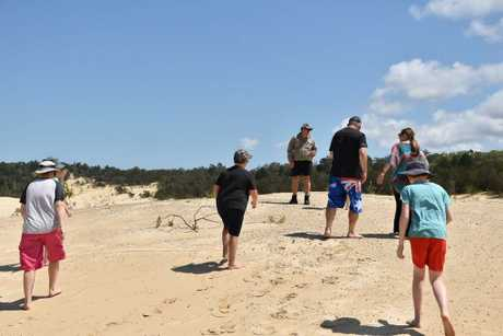 Tourists walk around Lightning Ridge on Moreton Island