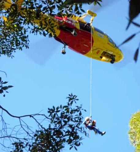 Vertical rescue: A helicopter crew member is winched to the girl.