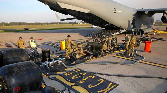 Australian Army and Royal Australian Air Force personnel fill collapsible fuel drums as part of a defuelling/refuelling trial.