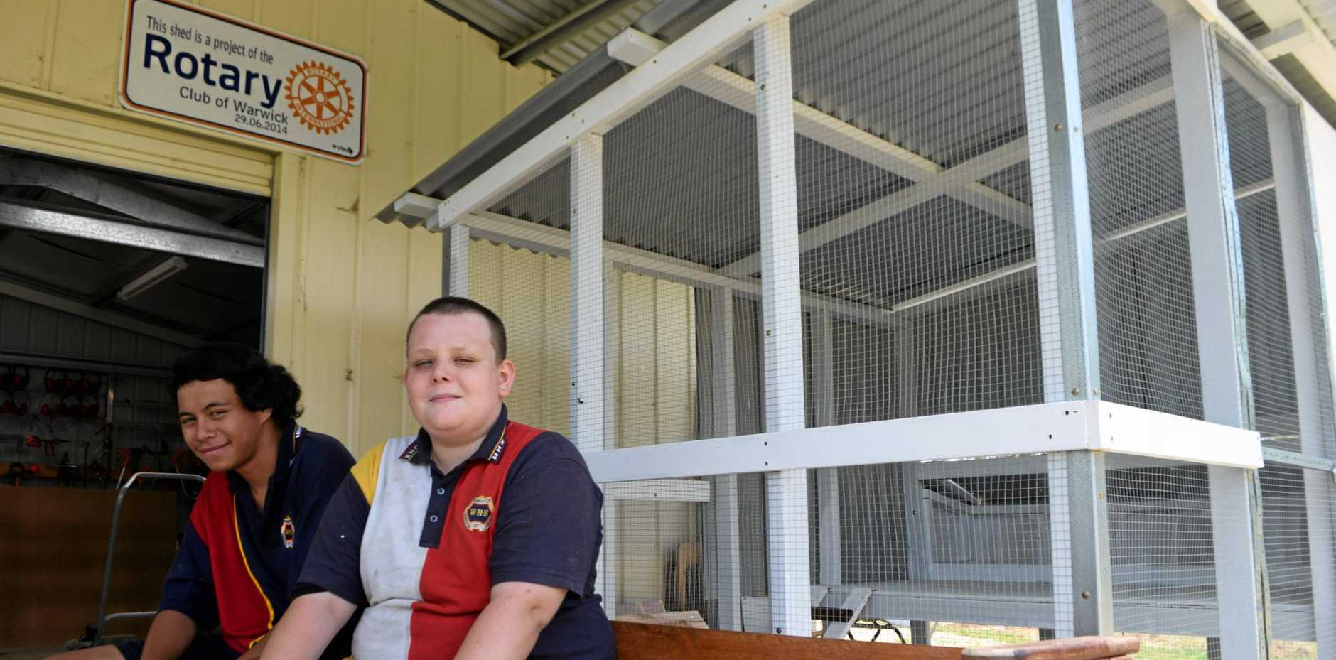 GIVING BACK: Hugh Connal and Jadein Martin from Warwick State High sit on the Buddy Bench next to the chicken coop they have built over the past few months.