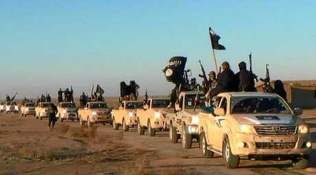 In this undated photo released by a militant website (verified and consistent with other AP reporting) ISIS militants hold up their weapons and wave flags on their vehicles in a convoy on a road leading to Iraq. The Islamic State group is notorious for the atrocities it has committed in recent times.