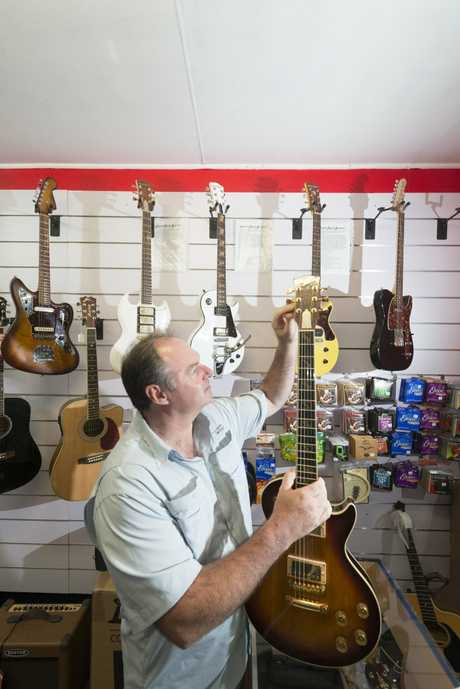 Paul Kneller of Garage Music with one of his Hard Road handmade guitars. Photo Adam Hourigan / The Daily Examiner