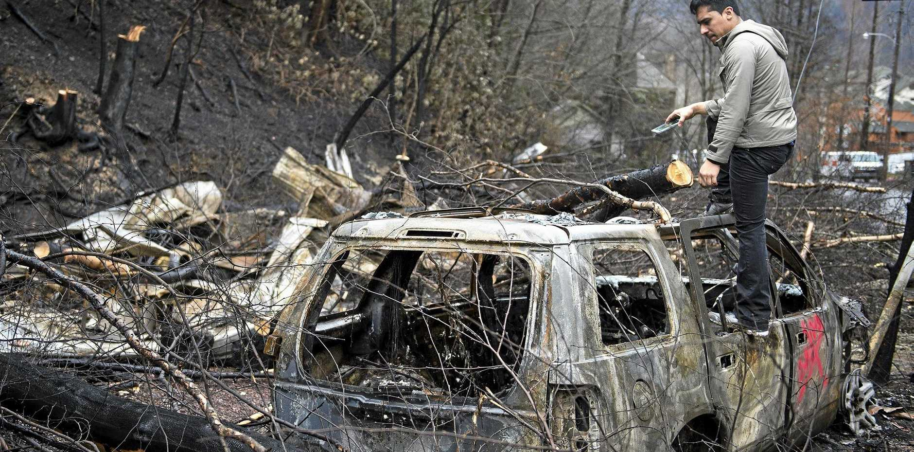 Allan Rivera looks over the remains of his home a week after hurricane-force winds whipped up fires that killed 14 people and damaged or destroyed 1700 buildings in the Great Smoky Mountains tourist region of the US.
