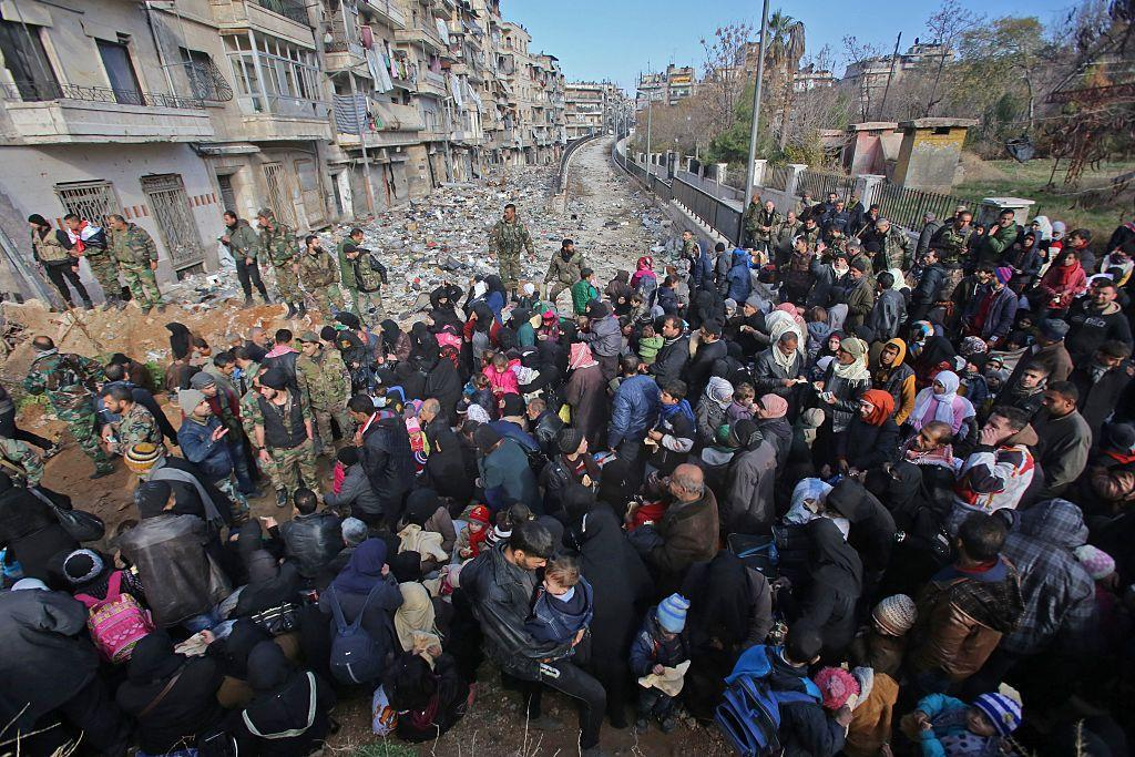 East Aleppo residents flee the violence at a checkpoint manned by pro-government forces in Maysaloun, Aleppo, on December 8 2016 AFP