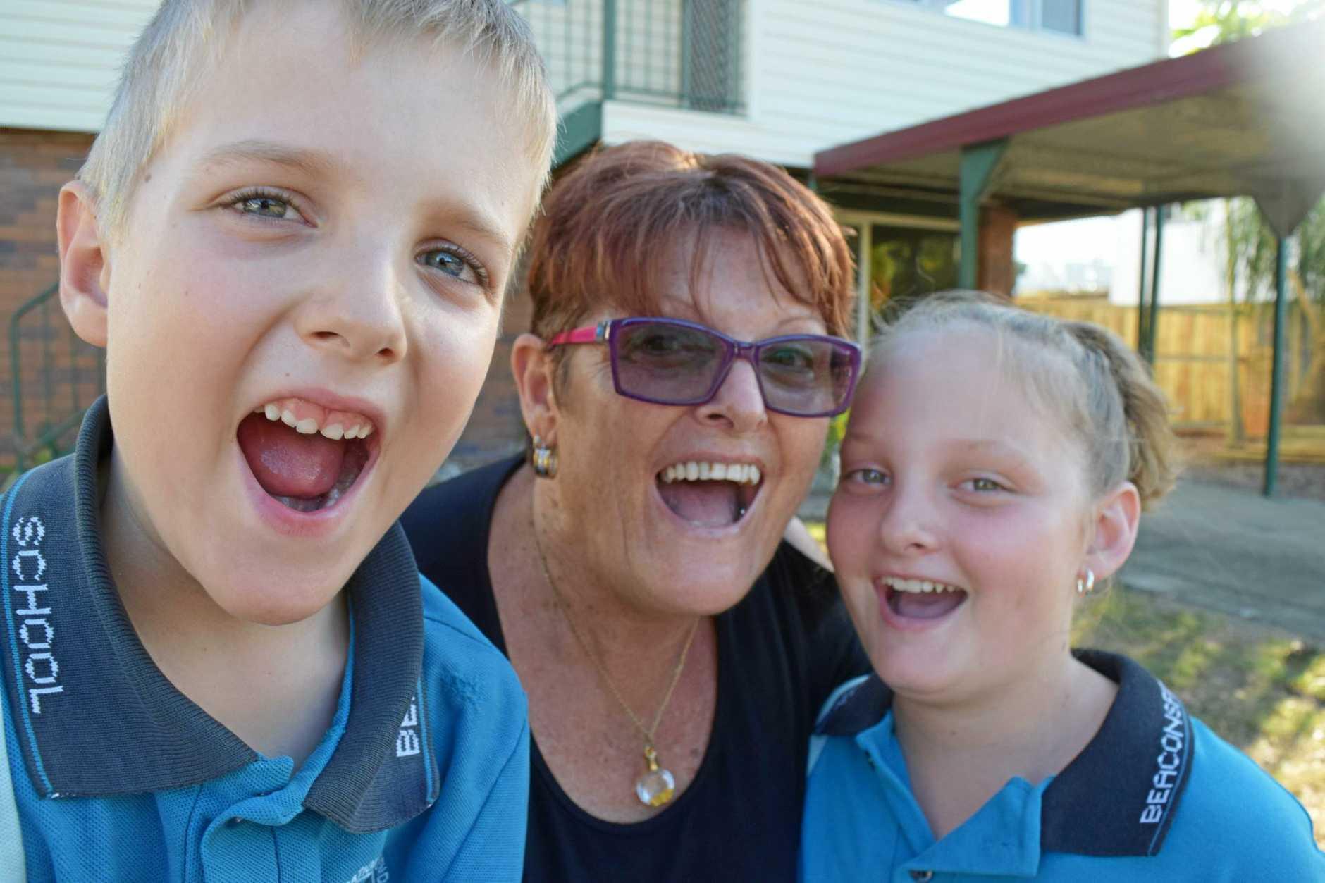 Logan Szkurda, 7, Dorothey Ramsamy, Eric Szkurda, 10, outside the family's new home in Beaconsfield