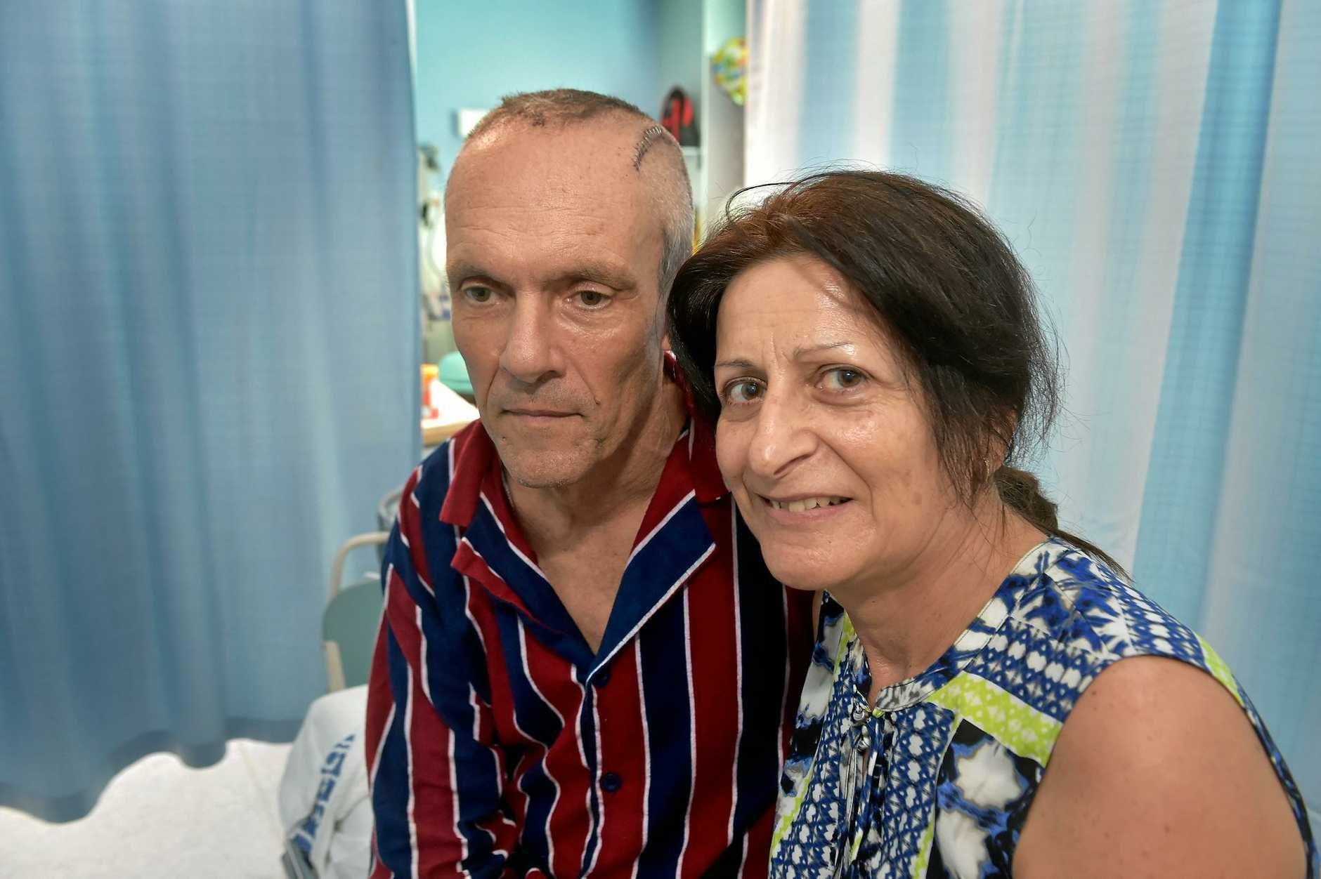 Former Coolum man Steve Nichol is recovering in a Brisbane hospital after a brain operation. Steve is comforted by his wife Angie.
