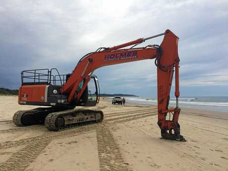 An excavator is being used at Lennox Head to retrieve debris from the failed eco barrier.
