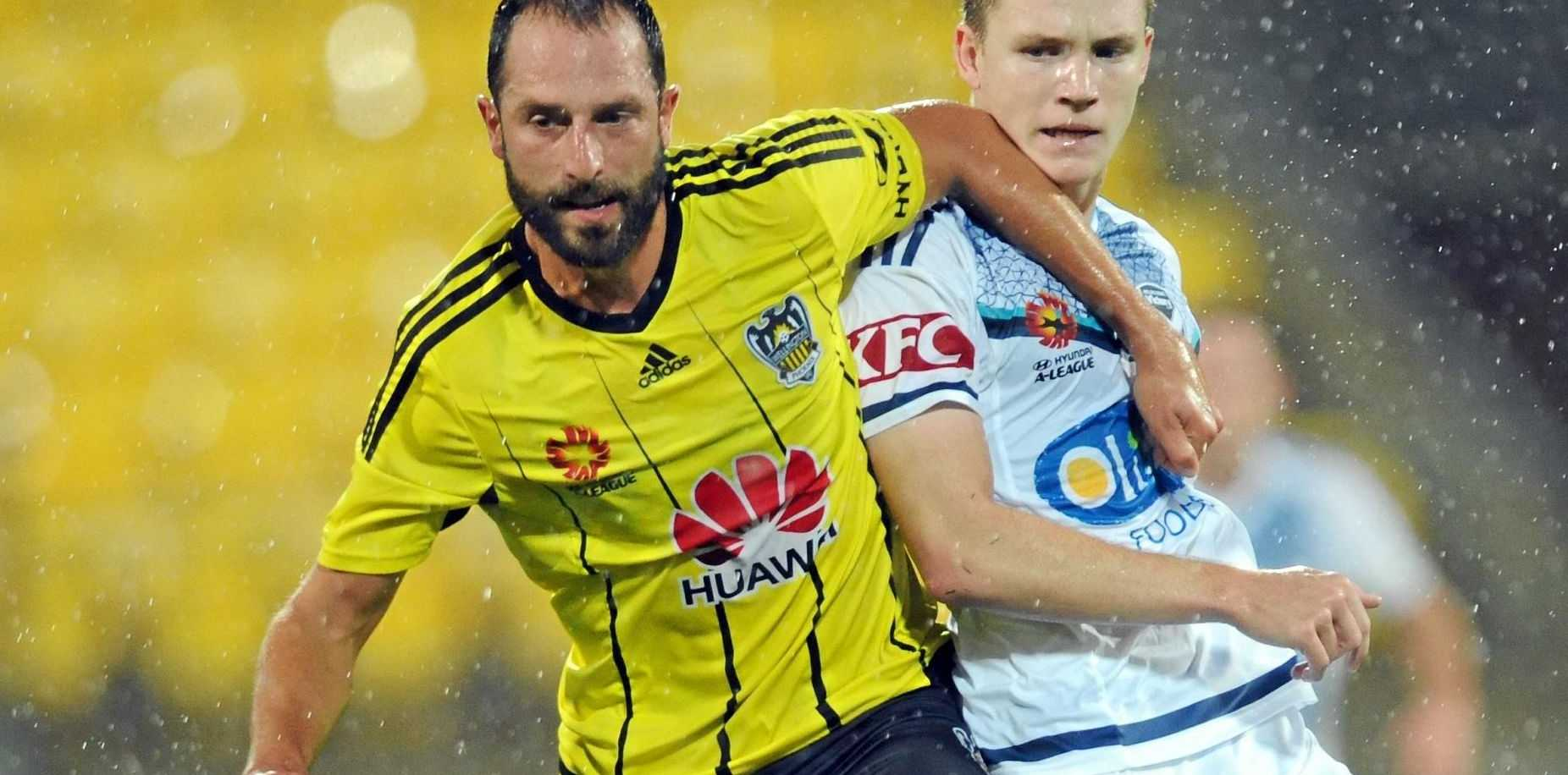 Wellington Phoenix's Andrew Durante (left) holds back Melbourne Victory's Scott Galloway.