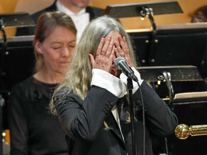 US singer Patti Smith covers her face when performing A Hard Rain's A-Gonna Fall by absent 2016 Nobel literature laureate Bob Dylan during the 2016 Nobel prize award ceremony at the Stockholm Concert Hall.