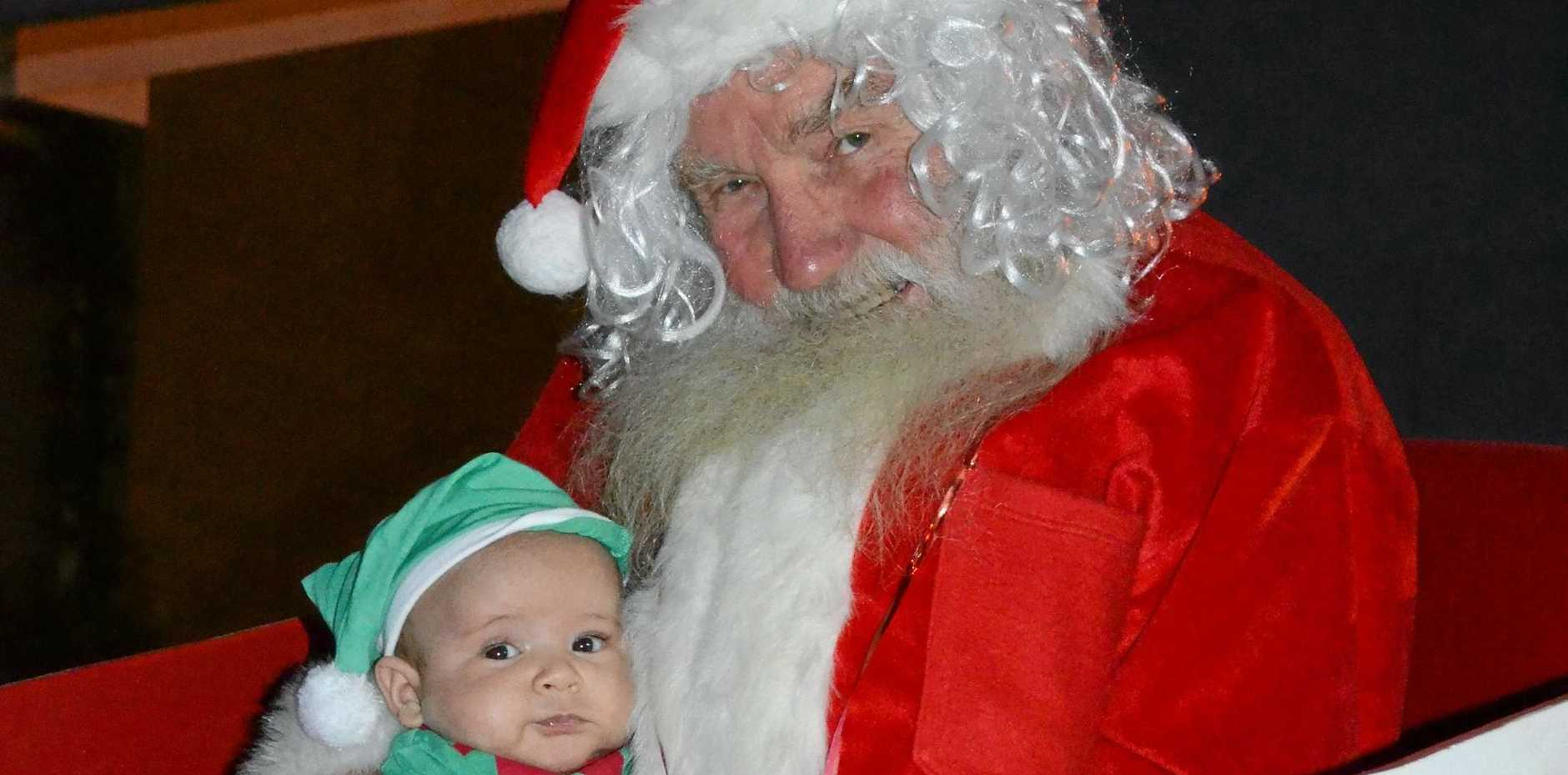 FUN FOR ALL AGES: Christmas elf Clancy Willett visited Santa Claus (Bill Humble) before Santa arrived at the Carols by Candlelight.
