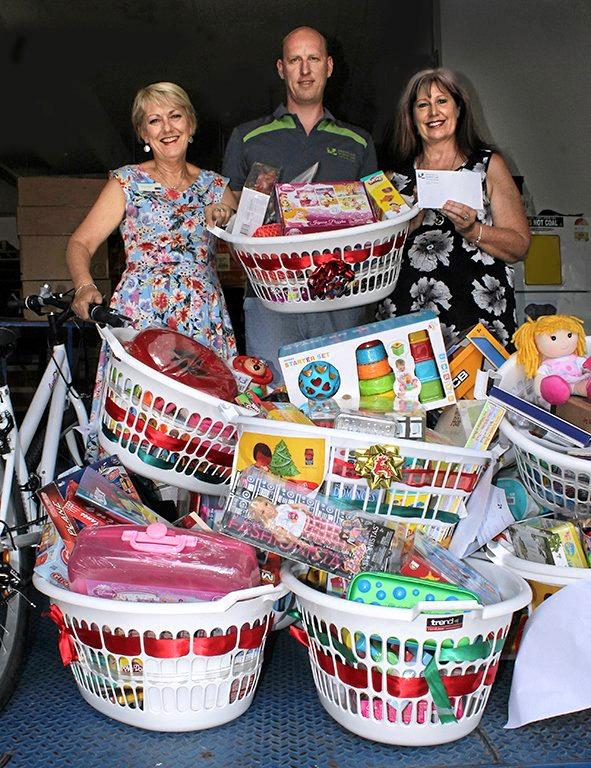 USC human resources adviser Tim Spratling present 15 baskets of gifts, along with $500 cash, to Nancy McCam and Marion Allan, of The Smith Family.