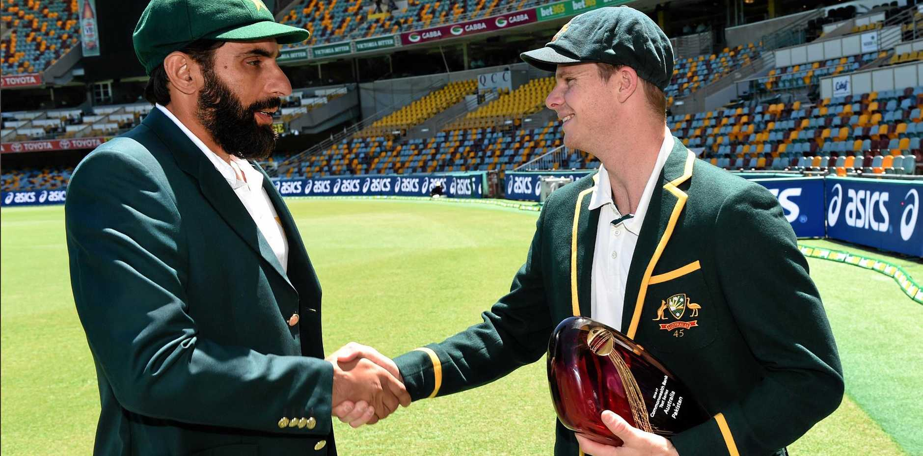 Australian cricket captain Steve Smith (right) and Pakistan captain Misbah-ul-Haq shake hands with the Test series trophy at the Gabba.