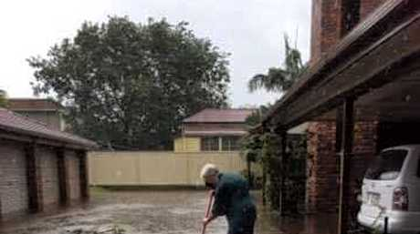 Colleen Mallet attempts to clean a blocked drain that caused flooding at her Booval home on Sunday
