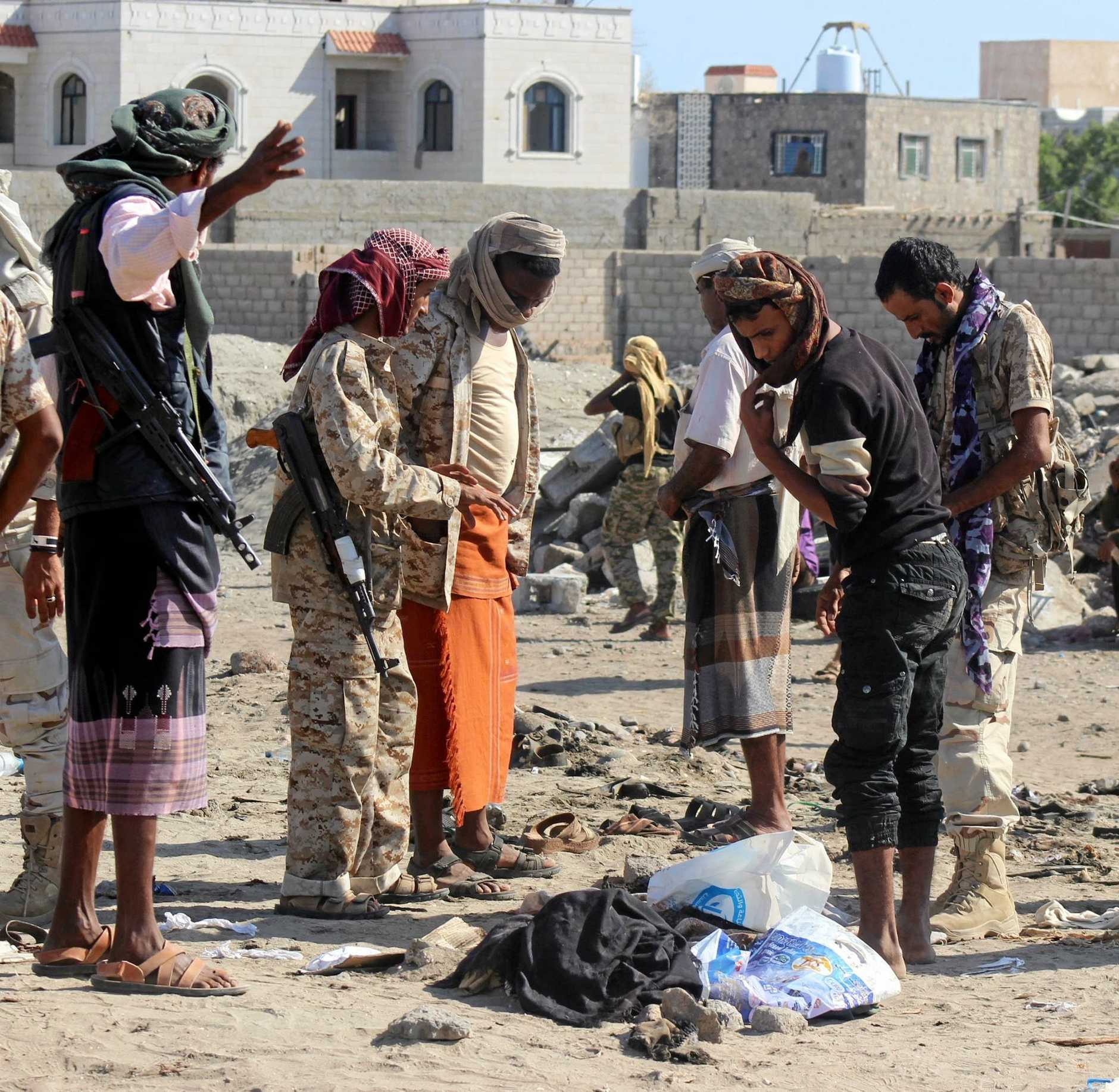 Yemeni residents and gunmen stand at the site of bombing that was targeting a military barracks in the southern province of Aden.