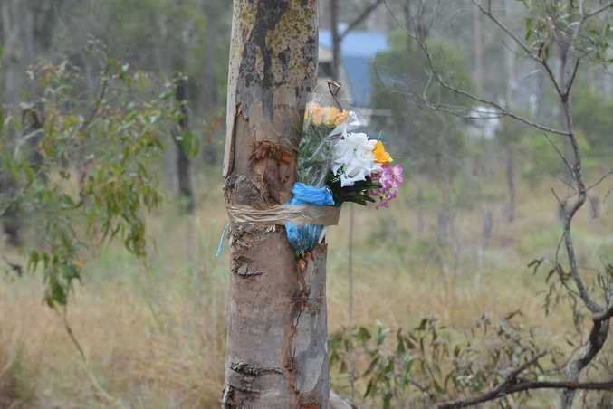 TRIBUTES LAID: Flowers are taped to the tree at the scene of a tragic crash in Bucca.