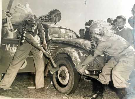 Garth (left) and his racing team bash out a panel after rolling the car end over end during a race in the 1950s.
