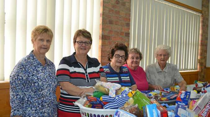 HELPING OUT: Cheryl Carletti, Kylie Burton-Beckett, Carmel Mahoney, Nancy Richardson and Doreen Williams with the gift baskets.