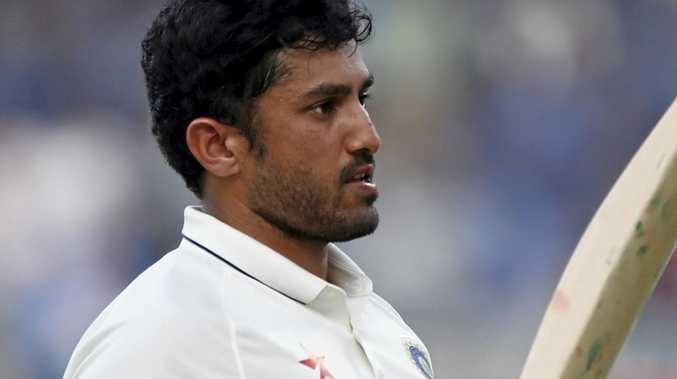 India's Karun Nair raises his bat after scoring a triple century against England.