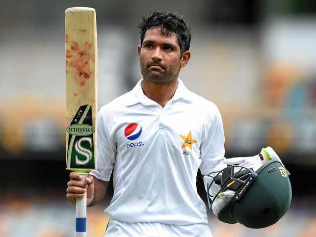 Pakistan batsman Asad Shafiq raises his bat as he walks from the Gabba.