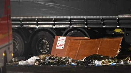 Damaged parts of a stalls lie against a truck at the scene after it crashed into a Christmas market, close to the Kaiser Wilhelm memorial church in Berlin