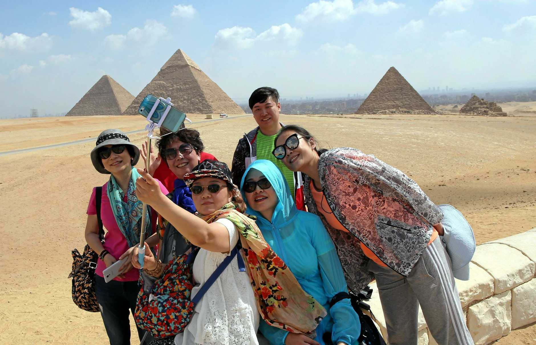 Tourists get a 'selfie' with the pyramids in Giza, Egypt. The tourism industry is one of the country's main sources of its much-needed foreign currency.
