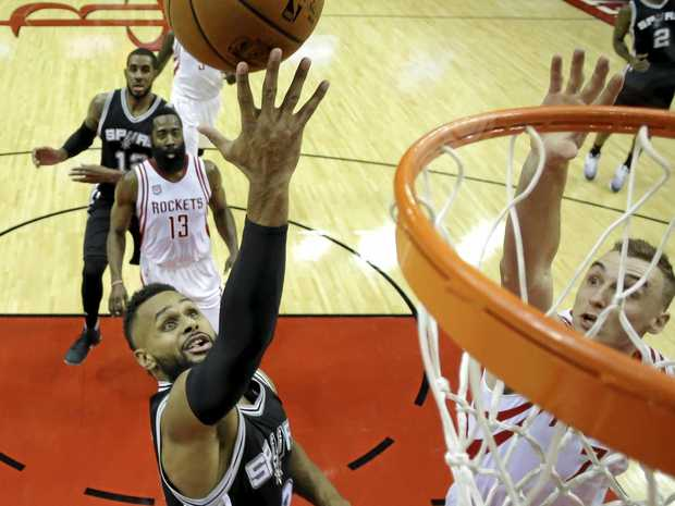 San Antonio Spurs star Patty Mills goes up for a shot as the Houston Rockets' Sam Dekker tries to block.