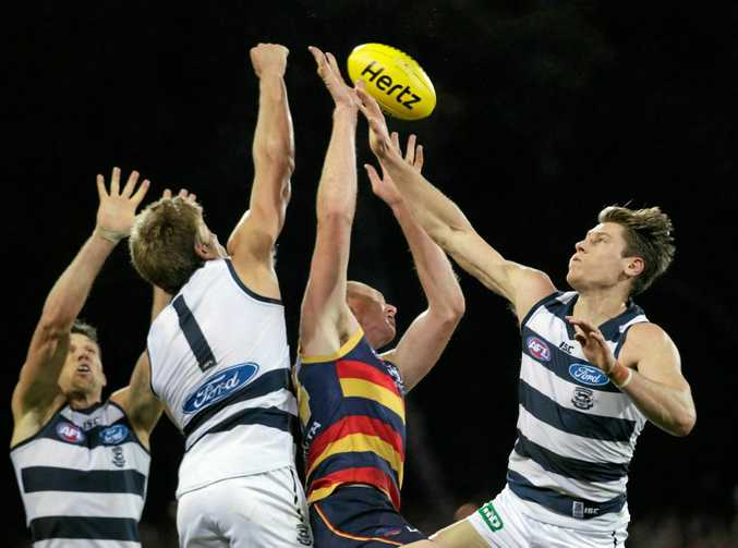 Rhys Stanley and Mark Blicavs of the Cats outnumber Sam Jacobs of the Crows at a throw-in.