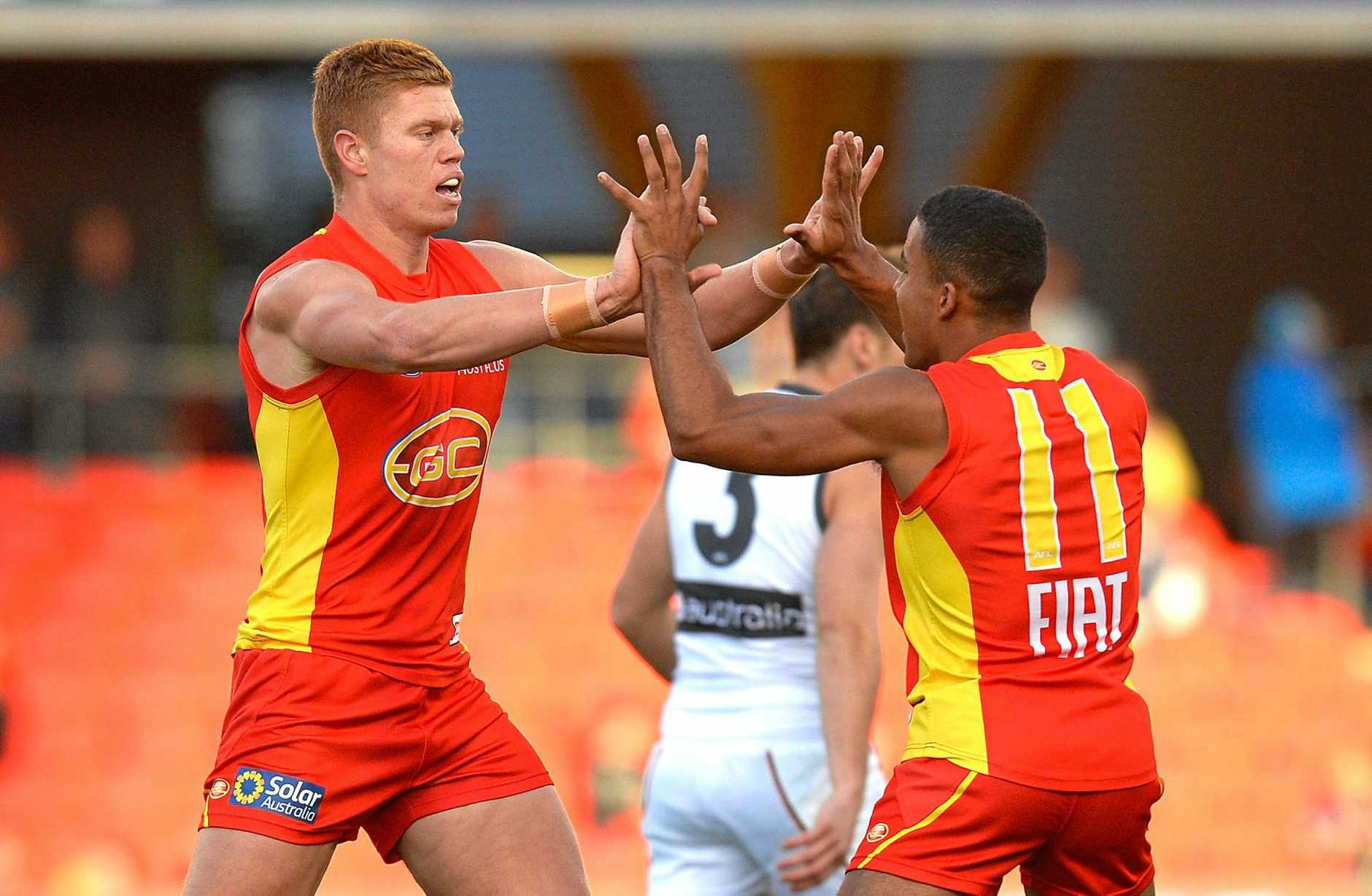 Peter Wright celebrates with teammate Touk Miller after kicking a goal for the Suns.