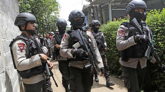 Officers stand guard outside a house used by suspected militants, in Tangerang, Indonesia.
