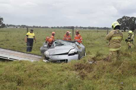 SES and NSW Fire and Rescue crews examine the wreckage of a car that flipped when it left the road in Junction Hill today.