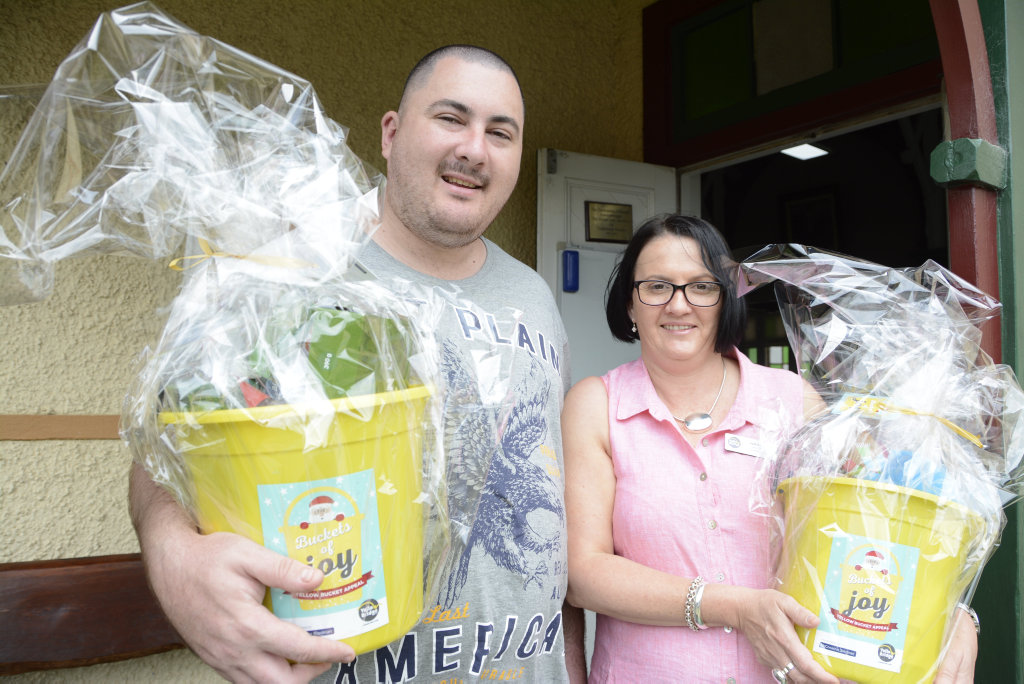 KIND GIFT: Toowoomba Clubhouse participant Luke Finlayson's Christmas got even brighter after he and hundreds of others received yellow 'buckets of joy' from YellowBridge, headed by Jodie Collins.