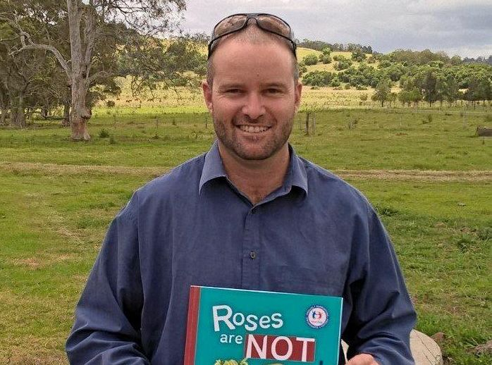 Scott Rheuben, of Lismore, with his children's book, Roses are NOT Red.