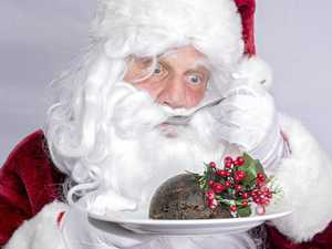 Close up portrait image of Santa Claus eating a Christmas pudding