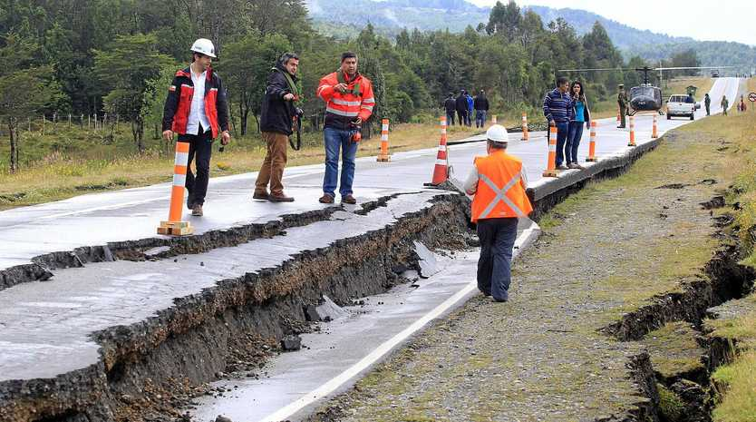 Workers inspect a section of road severely damaged by a 7.6 magnitude earthquake in Tarahuin, on the island of Chiloe, a town 1250km south of Santiago, Chile,