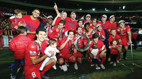 Adelaide United players celebrate winning the A-League grand final.