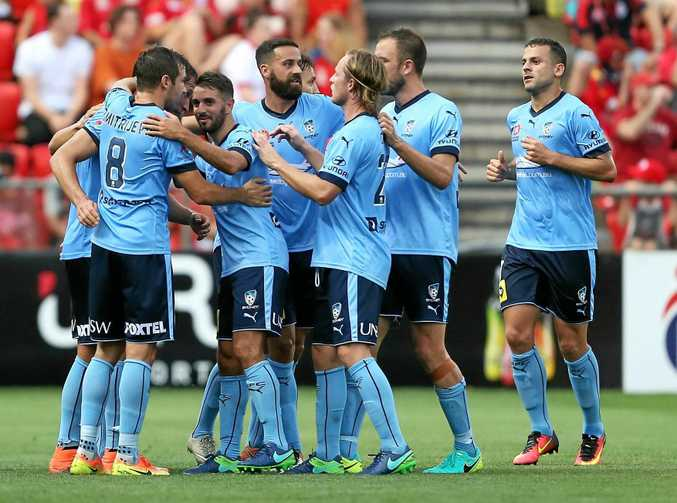 Sydney FC players celebrate after a Filip Holosko goal against Adelaide on Boxing Day. The Sky Blues are undefeated so far this season but face a stern test tomorrow night against the Brisbane Roar.