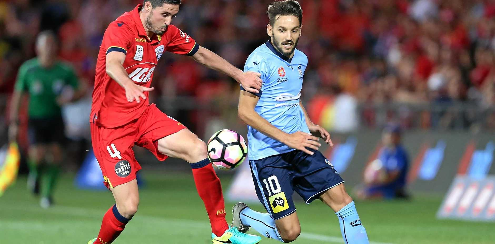 Dylan McGowan of Adelaide United (left) clashes with Milos Ninkovic of Sydney FC.