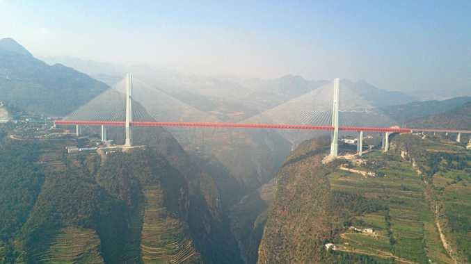 WOULD YOU DO IT? Nervous drivers face a crossing of more than 1.3km on the Beipanjiang Bridge Duge, with a drop of 565m to the river below.
