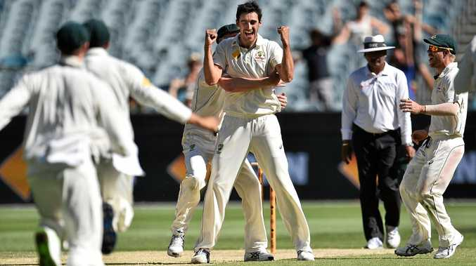Australian players embrace Mitchell Starc after his dismissal of Wahab Riaz.
