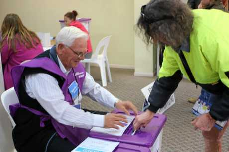 ELECTION: An Electoral Commission official helps a voter place his Senate paper in the ballot box.